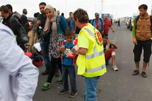 Een lid van de Maltezer Orde deelt voorraden uit aan vluchtelingen in Hongarije