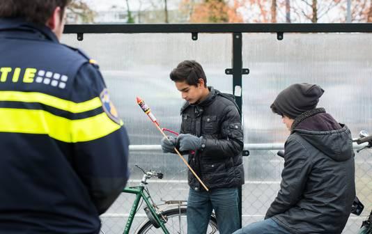 Een politieagent spreekt twee jongens aan die met vuurwerk aan het spelen zijn op straat. Verschillende gemeentes kondigen een vuurwerkverbod af op specifieke locaties.