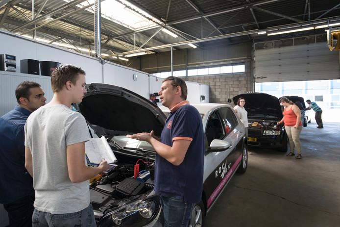 Een praktijkles van studenten autotechniek in hun tijdelijke onderkomen, een voormalige garage in Ede.