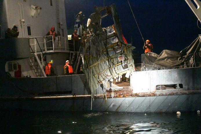 Een reddingsteam haalt wrakstukken uit de zee.