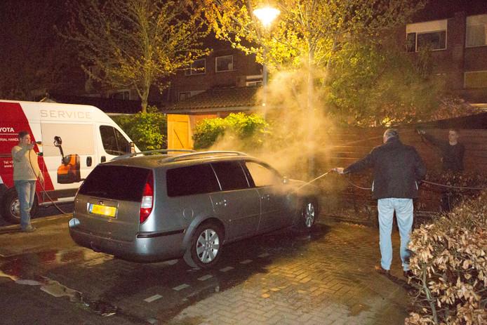 Buurtbewoners blussen de autobrand aan de Schoonenburg.