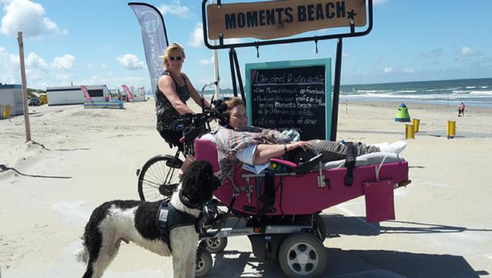 Begeleid door haar hulphond Uggs wordt Marja den Besten in haar rolstoel het strand bij Ter Heijde opgereden door Diane Olsthoorn. Het gemakkelijk toegankelijke strand vormde de uitgelezen mogelijkheid eindelijk weer eens zilte lucht te happen.