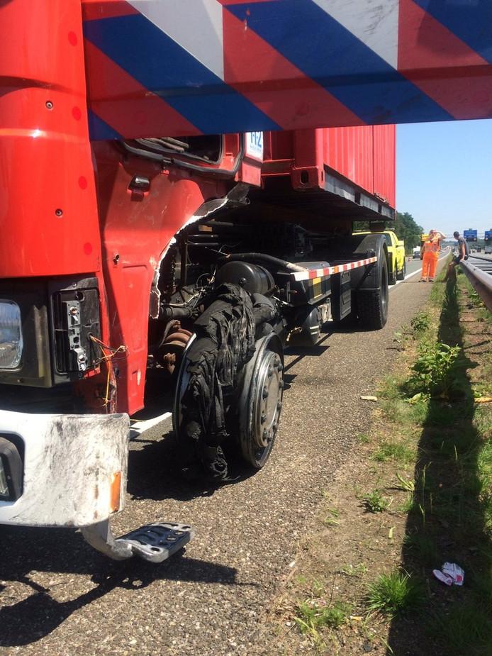 Het gestrande brandweervoertuig met de klapband langs de A12.