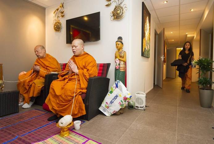 De monniken reciteren teksten met een katoenen draad in hun handen die hen verbindt met het Boeddhabeeld in de zaak. Foto Rolf Hensel.