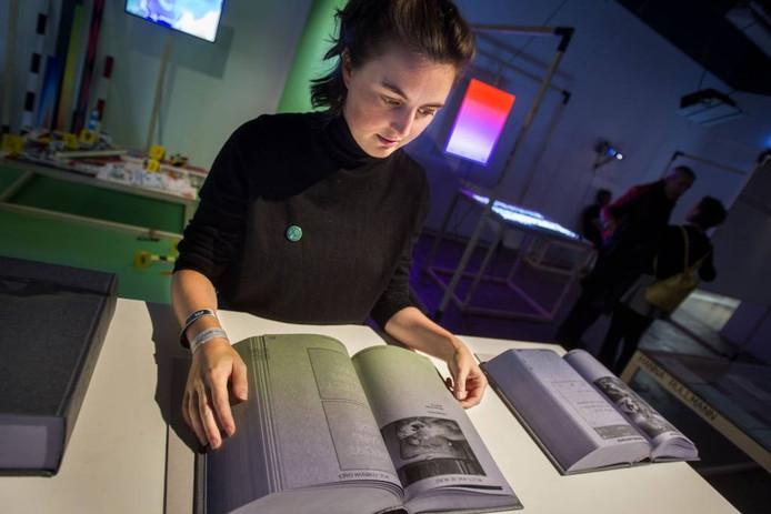 Dieuwertje Luitse toont het door haar gemaakte boek dat op de DDW deel uitmaakt van de expositie In Real Live van ArtEZ. Het geeft de reacties op sociale media weer op een kunstwerk Frank Denson.