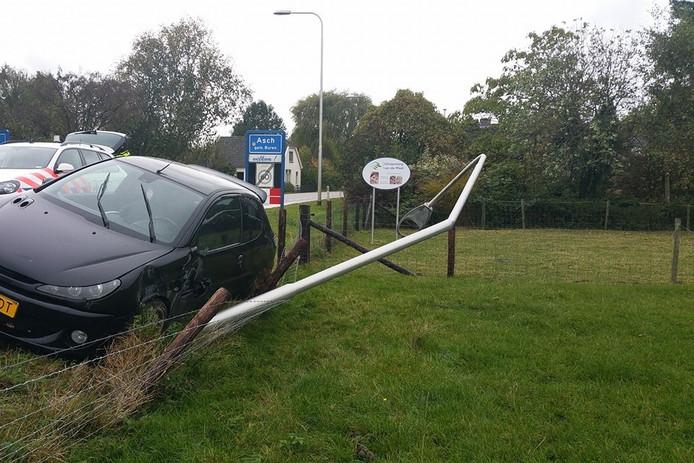 De lantaarnpaal en auto raakten flink beschadigd bij het eenzijdige ongeluk in Asch.