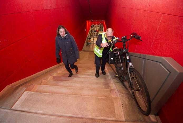 Een medewerker van de fietsenstalling onder Rozet helpt een vrouw haar fiets naar boven te rijden.