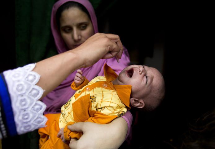Een baby in Pakistan krijgt het poliovaccin binnen gedruppeld