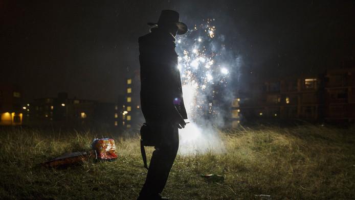 Een man steekt vuurwerk af tijdens de jaarwisseling.