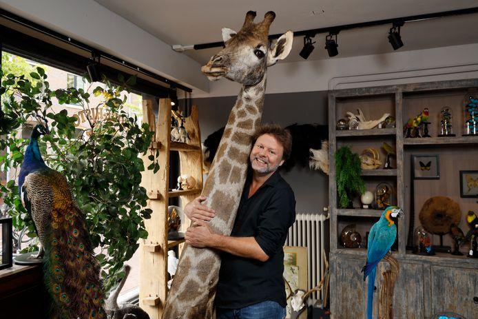 Erwin van Zoelen met een giraffe in zijn zaak in Nijmegen.