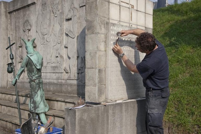 """Het uitkappen en schoonmaken van de in kalksteen gebeitelde tekst bij het Reynaertmonument aan de Gentse Poort in Hulst is volgens beeldhouwer Luc Ingels een tijdrovend werkje. """"Ik denk dat ik er alles bij elkaar wel een paar weken voor nodig heb."""" foto Mark Neelemans"""