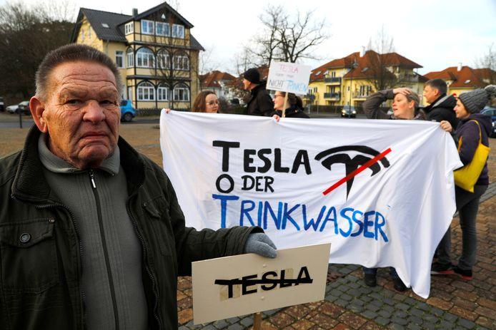 Demonstranten met anti-Teslabordjes en -spandoeken. 'Tesla of drinkwater' staat er op het spandoek.