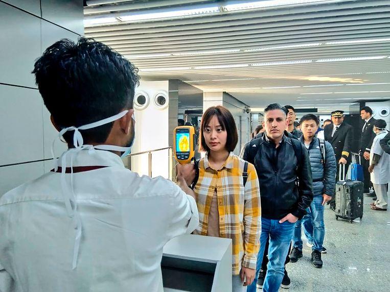 Passagiers uit China worden gescand op koort op het vliegveld van Kolkata, India. Beeld AFP