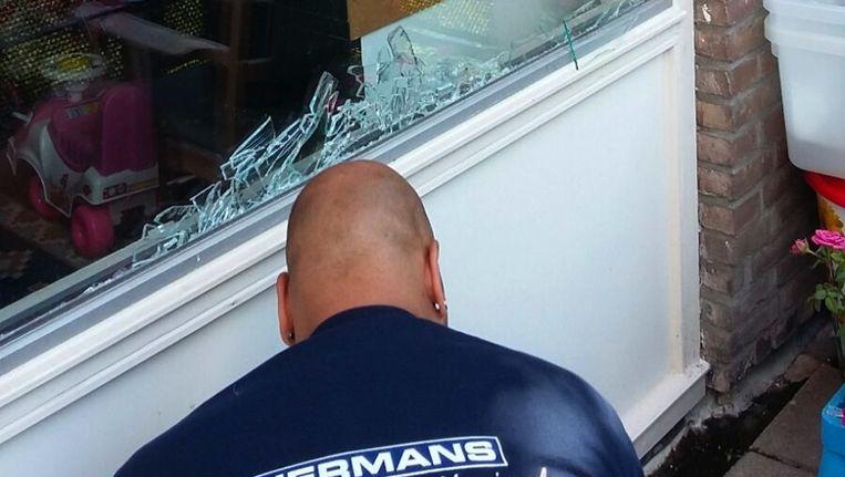 Een glaszetter vervangt het vernielde raam Beeld Hanneloes Pen