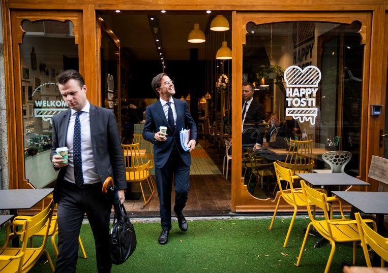 Premier Mark Rutte nadat hij een kop koffie heeft gehaald bij Happy Tosti op weg naar dag twee van de algemene politieke beschouwingen. Beeld Freek van den Bergh