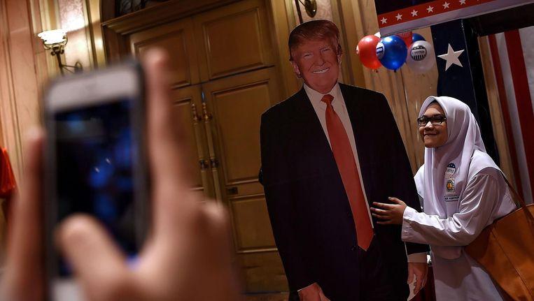 In Maleisië poseert een meisje bij een bordkartonnen Trump. Beeld afp