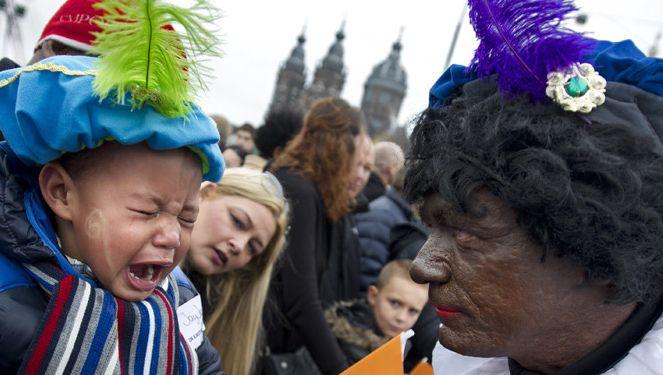 Een jongetje en een Zwarte Piet tijdens de intocht van Sinterklaas in Amsterdam vorig jaar.