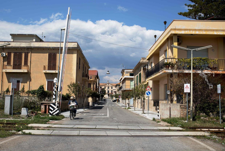 Een vrijwel lege straat in Locri, in de Italiaanse regio Calabrië. Het plaatselijke ziekenhuis kampt met haperende medische apparatuur, een tekort aan artsen en gebrek aan geld, mede door infiltratie van de maffia.  Beeld AFP