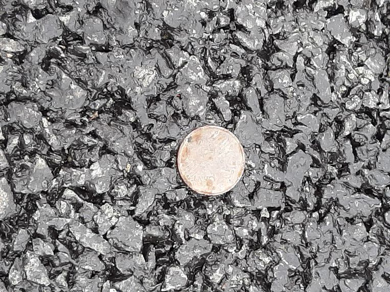 Een muntstuk is door een lollige wegwerker in het asfalt gedrukt. Beeld MARC KRUYSWIJK