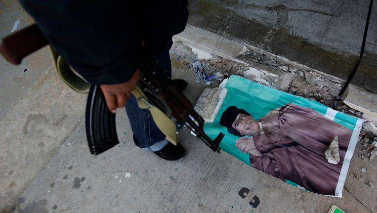 Een portret van Muammar Kaddafi op de grond. Beeld AP