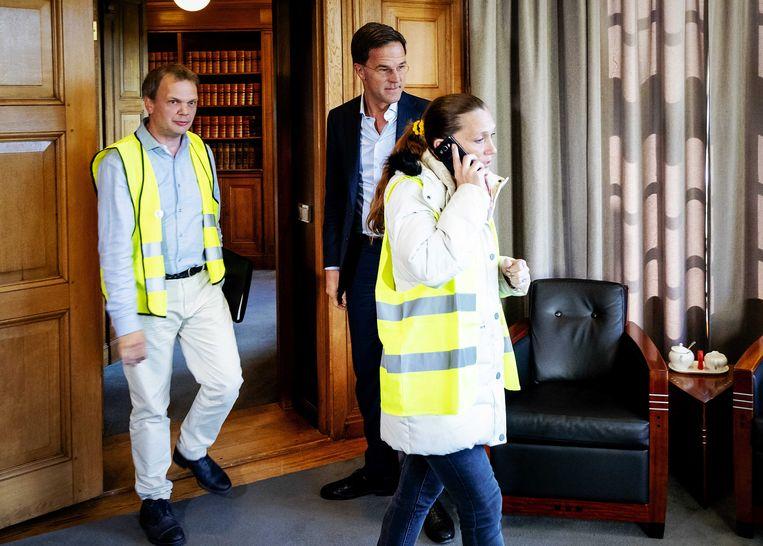 Hannie Descendré komt telefonerend binnen en weigert Rutte de hand te schudden  Beeld ANP