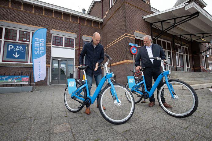 De wethouders Geert Meijering (l) en Albert Holtland namen vanmiddag de deelfiets in gebruik.