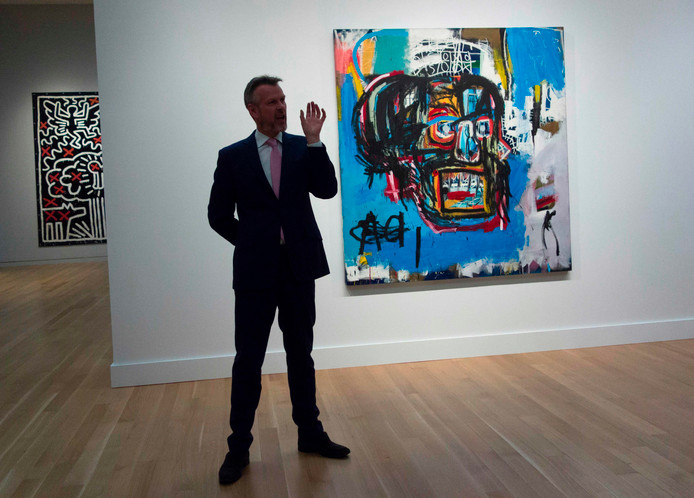 Een medewerker van Sotheby's bij het kunstwerk vanJean-Michel Basquiat. Het werk is gekocht door een Japanse miljardair.