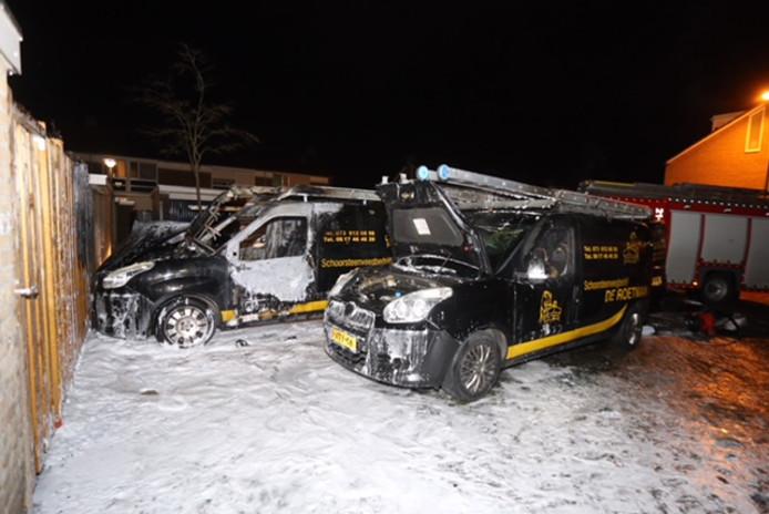 De brandweer blust de bedrijfsauto's die in brand stonden.