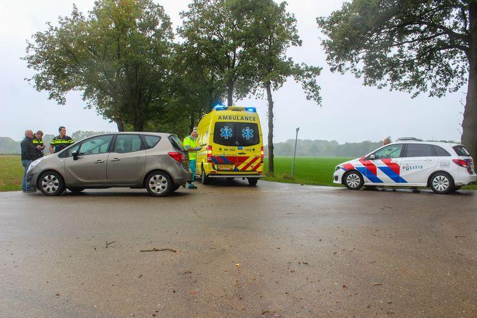 Verbouwereerd praat de bestuurder van de auto die de scooter raakte, een politieagent bij.