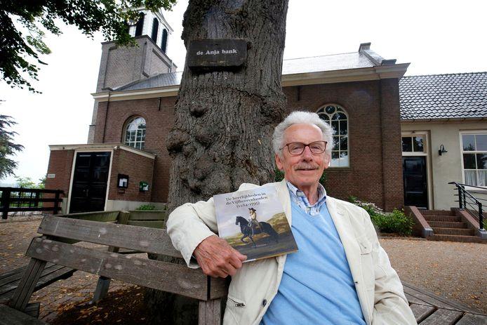 Teun Bikker laat zijn boek zien met op de achtergrond het kerkje in Oosterwijk waarin Ambachtsheer Willem van Liere is begraven.