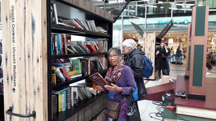 Toine Huliselan zoekt boeken uit bij de nieuwe boekwissel in het centraal station van Utrecht.