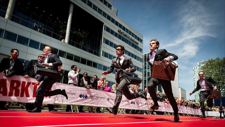 Consultants, bankiers, juristen en ambtenaren gaan voor de winst tijdens de Hakken/Pakken Run op de Zuidas in Amsterdam. Beeld anp