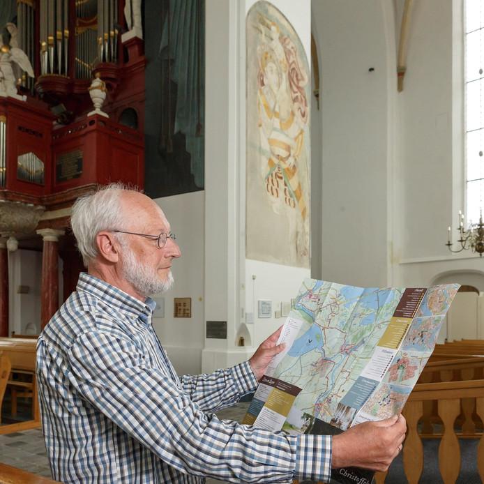 Wim Zwitser met de kaart van het Christoffelpad in de Grote of Stephanuskerk in Hasselt, waar de beschermheilige hoofdpersoon is op een muurschildering.