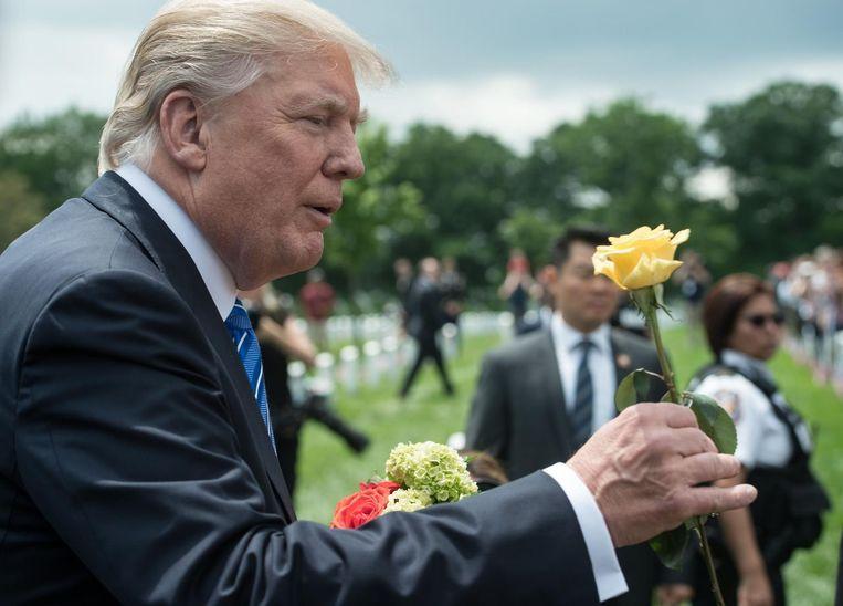 President Trump krijgt een roos aangeboden maandag tijdens een plechtigheid op de militaire begraafplaats Arlington in Washington. Daar werden de militairen herdacht die zijn gedood tijdens Amerika's oorlogen. Beeld AFP