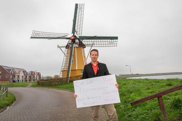 """Ralph van Hertum bij de molen in Sint-Philipsland. De symbolische cheque van 10 miljoen euro droeg hij over aan de lokale Pvda/GL-fractie. ,,Laat dat geld ten goede komen aan de mensen van Tholen."""""""