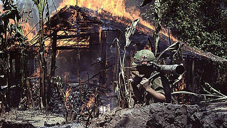 Een Amerikaanse soldaat loopt langs een brandend dorp in My Tho, Vietnam, 1968. Beeld afp