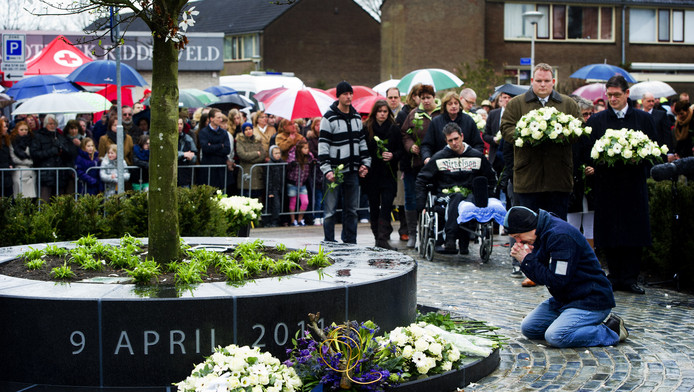Een belangstellende knielt bij het nieuwe monument tijdens de herdenking van de schietpartij in winkelcentrum de Ridderhof in Alphen aan den Rijn