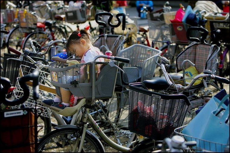 Slapend meisje in kinderzitje op geparkeerde fiets in Tokio. Beeld anp