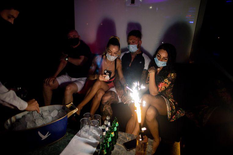 Mensen met een mondkapje in een nachtclub in Madrid. In Barcelona moesten de nachtclubs weer dicht vanwege een opleving van het coronavirus.  Beeld AP