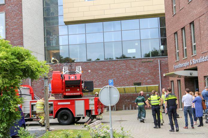 De brandweer controleert de buitenmuur waar het brandje is ontstaan.