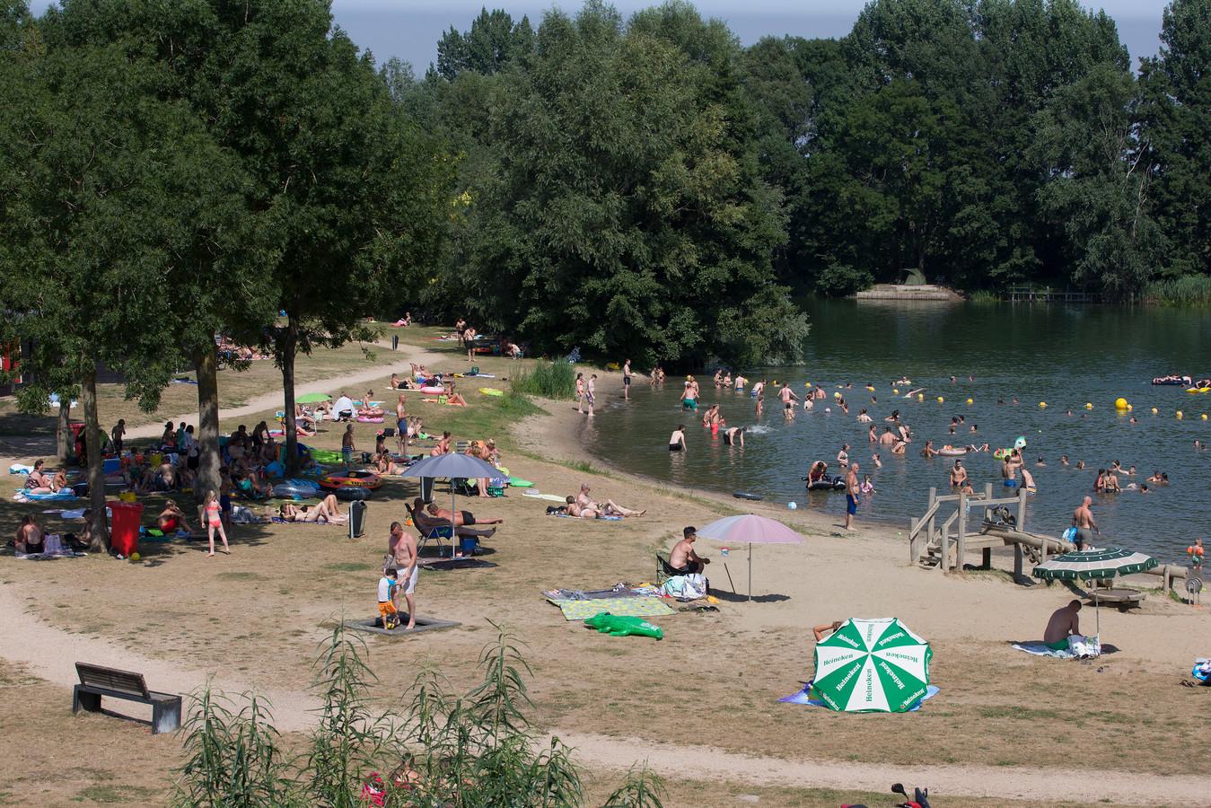 Mensen zoeken verkoeling in het natuurwater van De Breuly bij Zevenaar.