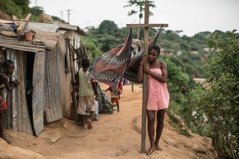 Een meisje staat bij de was in een arme buurt in Cabinda, de regio waar de helft van de Angolese olie vandaan komt. Beeld The Washington Post/Getty Images
