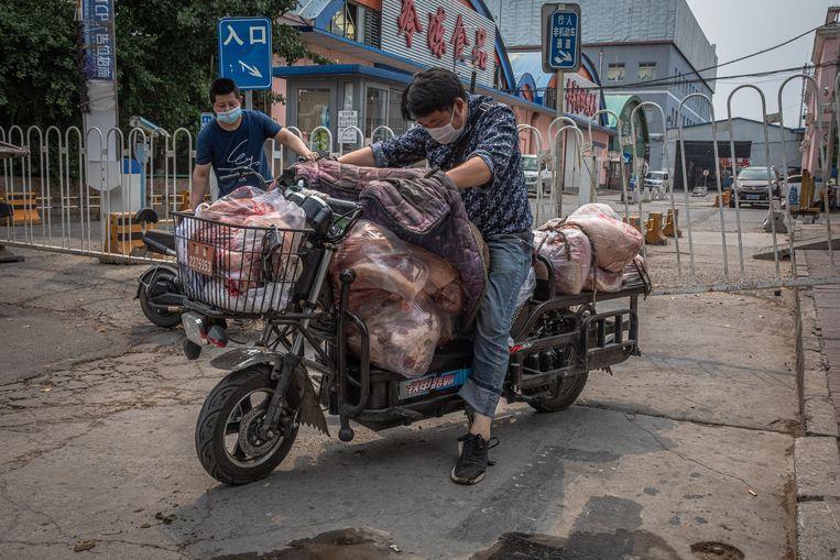 Een man op een met vlees volgepakte scooter nabij de groothandelsmarkt in Fengtai. Beeld EPA
