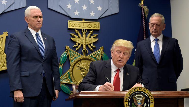 President Trump tekent zijn decreet over de nieuwe maatregelen tegen vluchtelingen. Hij wordt geflankeerd door vice-president Mike Pence (L) en minister van defensie James Mattis. Beeld AP