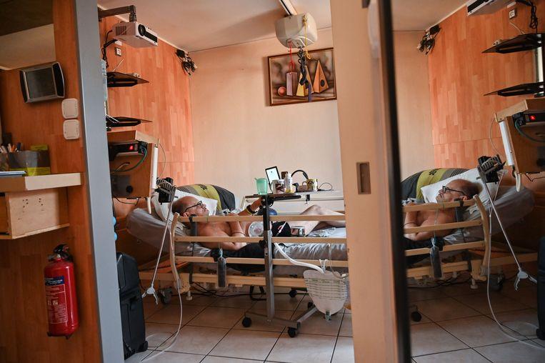 Alain Cocq op bed in zijn appartement. De Fransman kan vanwege de wet geen euthanasie krijgen en mag zijn dood ook niet livestreamen op Facebook.  Beeld AFP