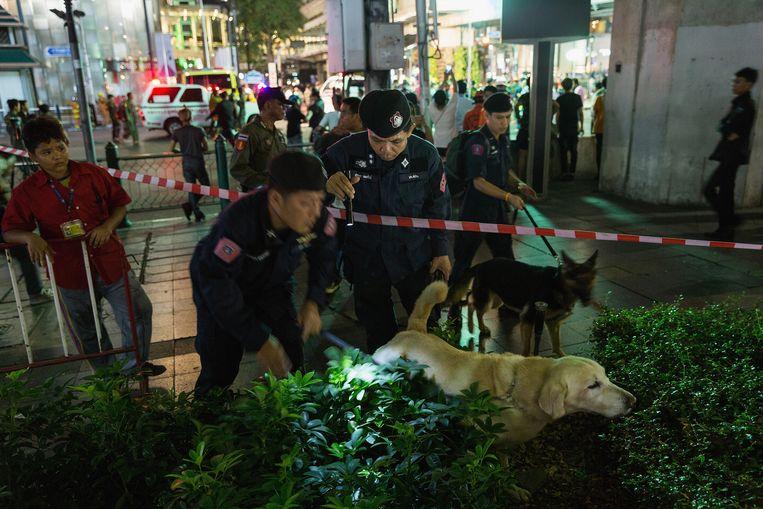 Politieagenten en speurhonden in de buurt van het kruispunt in Bangkok waar vanavond een bom ontplofte.