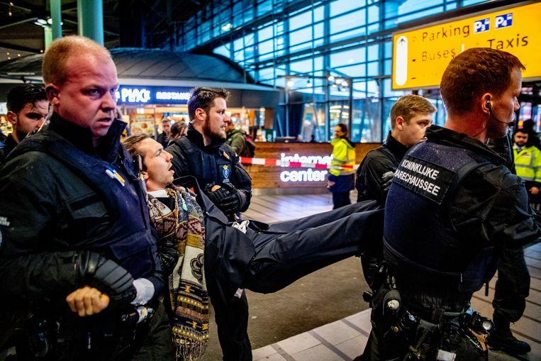 De Marechaussee verwijdert een actievoerder van Greenpeace uit Schiphol Plaza. Demonstranten protesteerden tegen de in hun ogen grote vervuiler Schiphol. Beeld ANP