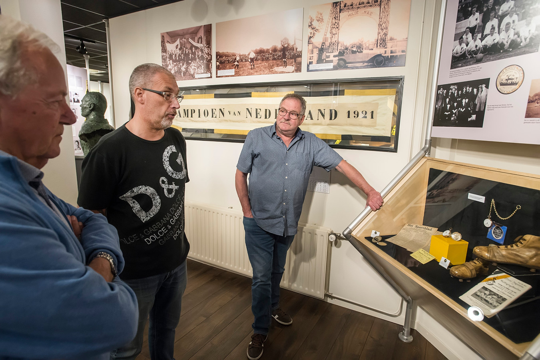 Wim de Bont, John de Leeuw en Ad van den Bemt bekijken onder andere  het kampioenshorloge uit 1921. Op de achtergrond het kampioensvaandel.
