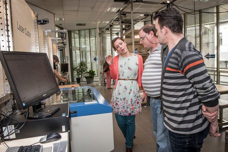 Een medewerker legt uit hoe de 3D-printer werkt.