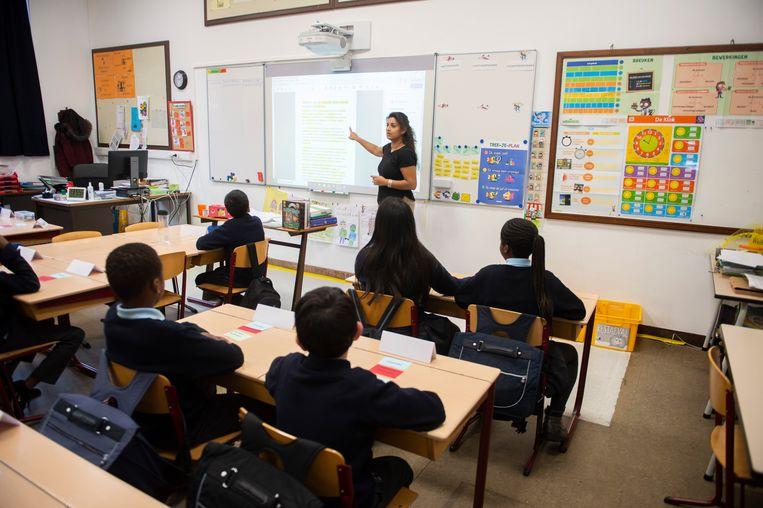 Juf Jinnih Beels helpt met een spelletje de leerlingen van het vierde leerjaar in het Sint-Jan Berchmanscollege op weg om de verschillende woordsoorten te leren.